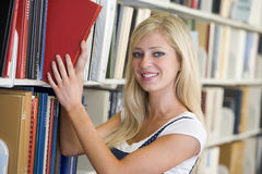 University student selecting book from library. Female student selecting book from library shelf stock photos