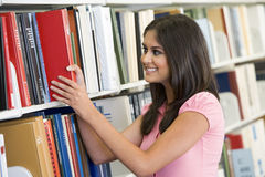 University student selecting book from library. Female university student selecting book from library shelf Stock Image