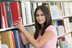 University student selecting book from library. Female university student selecting book from shelf royalty free stock photos