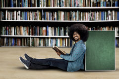 University student sitting with book and board. University student sitting with copy space on board while holding a book in the library Royalty Free Stock Photography
