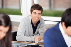 University Student Sitting At Desk With Classmates Royalty Free Stock Photo
