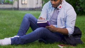 University student sitting on grass, writing essay, literary studies project. Stock footage stock footage