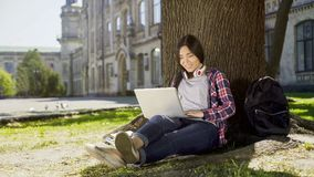 University student sitting under tree in campus, using laptop, smile on her face Royalty Free Stock Image
