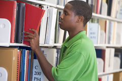 University student slecting book from library shel. Male student selecting book from library shelf Stock Image
