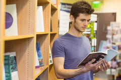 University student standing reading textbook Royalty Free Stock Images