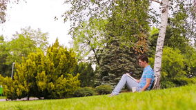 University student studying for exams outdoors in the park. With him his books, notebook, backpack and coffee. Young man studying for college exam in park stock video