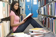 University student studying in library. Female student sitting on library floor surrounded by books royalty free stock photo
