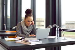 University student studying using laptop. Pretty young woman sitting in library using laptop smiling. Young woman sitting at table surfing internet for notes for Stock Photo