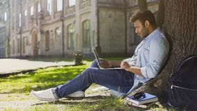 University student under tree, using laptop looking surprised, upsetting news Royalty Free Stock Photography