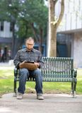 University Student Using Digital Tablet On Campus. Male university student using digital tablet on bench at campus Stock Images