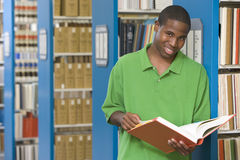 University student working in library. University student studying book in library stock photo