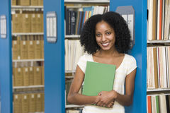 University student working in library. University student holding book in library stock photography
