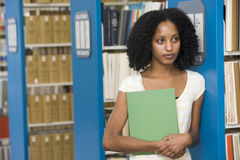 University student working in library. University student with textbook in library royalty free stock photography