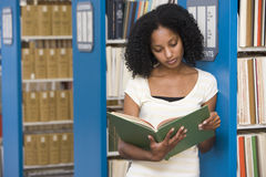 University student working in library. University student reading book in library stock images