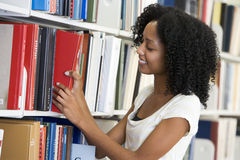 University student working in library. Female university student selecting library book from shelf royalty free stock photos