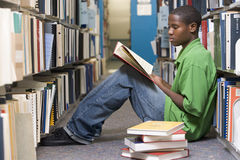 University student working in library. Male university student sitting on library floor surrounded by books royalty free stock photo