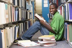 University student working in library. Male university student sitting on library floor surrounded by books Royalty Free Stock Photography
