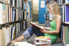 University student working in library. Female student sitting on library floor surrounded by books royalty free stock image