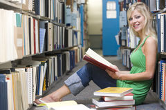 University student working in library. Female student sitting on library floor surrounded by books stock photo