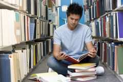 University student working in library. Male university student sitting on library floor surrounded by books stock images