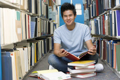 University student working in library. Male university student sitting on library floor surrounded by books Stock Photos