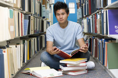University student working in library. Male university student sitting on library floor surrounded by books Stock Photo