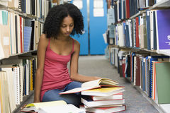 University student working in library. Female student sitting on library floor surrounded by books royalty free stock photos