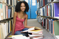 University student working in library. Female student sitting on library floor surrounded by books stock photography