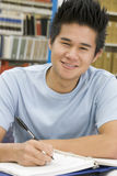 University student working in library. Male university student writing report in library Stock Photo