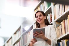 Young female student studying in the library Royalty Free Stock Photo