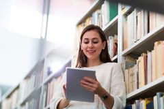 Young female student studying in the library Stock Images