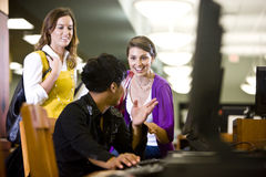 University students conversing by library computer. Male college student using computer and conversing with two pretty female students Royalty Free Stock Images