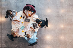 University students doing group study. Top view of group of students sitting together at table. University students doing group study Stock Photography