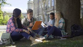 University students gathered under tree, having discussion, working on project. Stock footage stock video