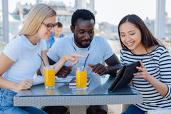 University students going out together in downtown. Check this out. Cheerful college friends sitting at a cafe table and focusing their attention on a screen of Royalty Free Stock Photos