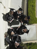 University students in graduation gowns and mortar boards holding diploma, portrait, overhead view royalty free stock photo