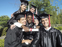 University students in graduation gowns and mortar boards holding diplomas, smiling, portrait royalty free stock photo