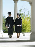 University students in graduation gowns and mortar boards walking in colonnade, holding diplomas Royalty Free Stock Image