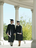 University students in graduation gowns and mortar boards walking in colonnade, holding diplomas Royalty Free Stock Photography