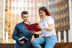 University. Students learning for exam together in a city park on university background. Students Brainstorming Meeting learning for exam. Fast learning concept stock photography