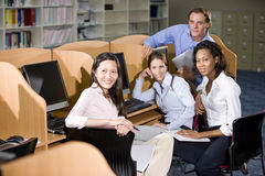 University students sitting  at library computer. Diverse university students sitting  at library computer studying together Stock Photos