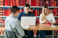University students sitting together at table with books and laptop. Happy young people doing group study in library.  Stock Image