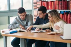University students sitting together at table with books and laptop. Happy young people doing group study in library royalty free stock photo