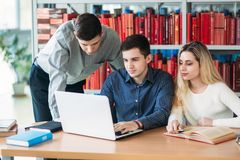 University students sitting together at table with books and laptop. Happy young people doing group study in library stock photos