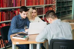 University students sitting together at table with books and laptop. Happy young people doing group study in library royalty free stock photos