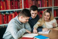 University students sitting together at table with books and laptop. Happy young people doing group study in library royalty free stock image