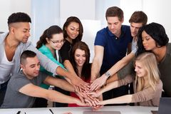 University students stacking hands at desk Stock Photos