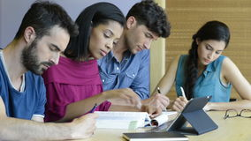 University students studying. Closeup shot of young man and woman discussing on note. Happy and smiling student studying at the library. Multi ethnic group stock video