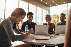 University students studying together in class. Beautiful young women reading book with classmates studying in background. University students studying together Stock Photo