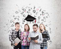 University students about to graduate. University students standing near concrete wall with sketches on it with graduation hat floating above them. Concept of Stock Images